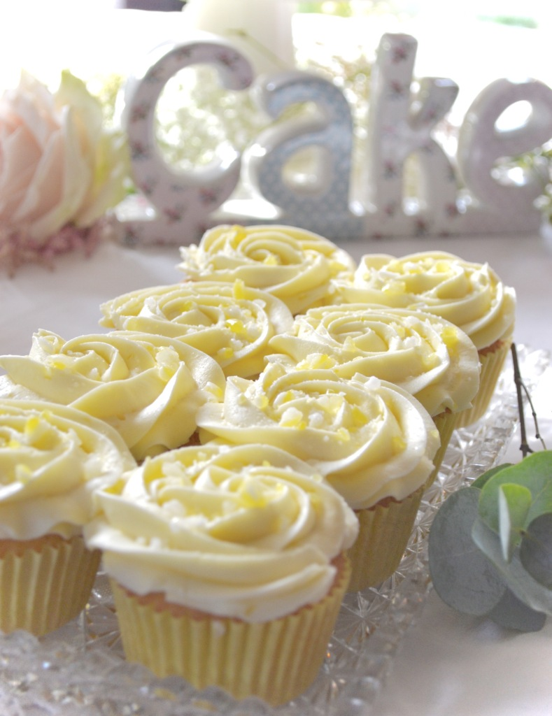 Lemon Cupcakes topped with a lemon buttercream rose and crushed lemon meringue sweets.