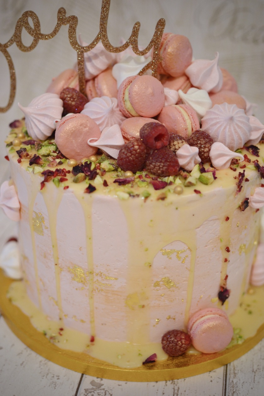 A jumble of Raspberry Macarons, Pistachio Macarons, Meringue Kisses, fresh Raspberries, chopped Pistachios, edible Rose Petals, Freeze Dried Raspberries and Gold Sugar and Balls.